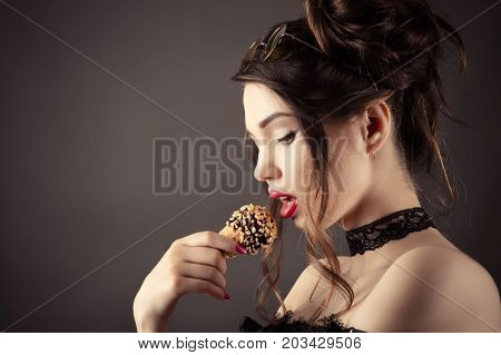 beautiful sexy woman eating ice cream isolated on gray background