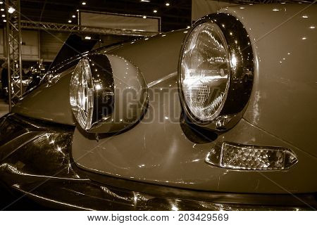 MAASTRICHT NETHERLANDS - JANUARY 08 2015: Headlamp of a mid-size luxury car Citroen DS21 Break. Stylization. Sepia. International Exhibition InterClassics & Topmobiel 2015