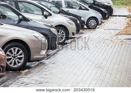 Several Cars Parked In A Parking Lot On Rainy Day