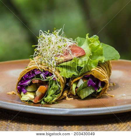 Raw vegan carrot and cumin wrap roll stuffed with shred lettuce tomato avocado spinach and savory zucchini hummus . Island Bali Ubud Indonesia