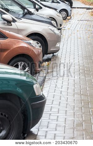 Row Of Cars On Parking Lot On Rainy Day