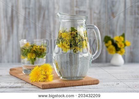 Dandelion yellow flower and green leaves tea vegetarian drink mortar vitamins health wooden background