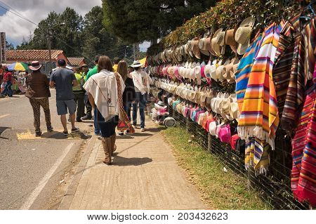 August 6 2017 Medellin Colombia: tourists walk by hats and ponchos hung on the fence by vendors during the flower festival in the Piedra Gorda area