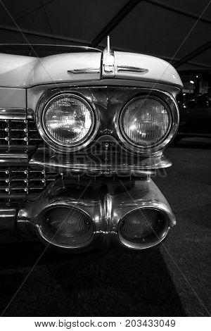 MAASTRICHT NETHERLANDS - JANUARY 08 2015: Headlamp of a full-size luxury car Cadillac Fleetwood Series 75 1959. Black and white. International Exhibition InterClassics & Topmobiel 2015