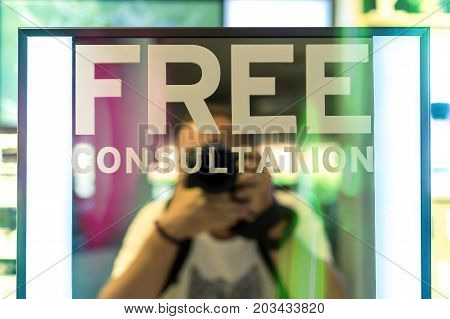 Free Consultation text in the mirror. Photographer behind. Free Consultation concept for any business.
