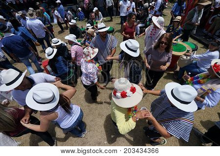 August 6 2017 Medellin Colombia: tourists wearing sombreros and ponchos dancing outdoors during the flower festival long weekend