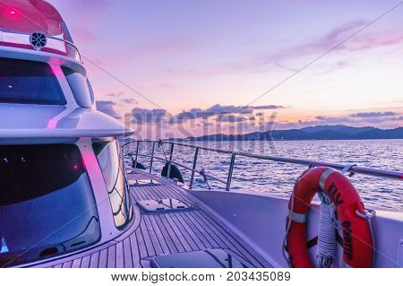 langkawi, Malaysia - 4th May 2017: Deck of a ship shot during the purple light of dusk. The wooden deck, beautiful curved glass and modern shape show the luxury and beauty of these modern ships
