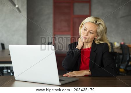Portrait of stressed young Caucasian businesswoman wearing red dress and jacket working at laptop and rubbing neck in office