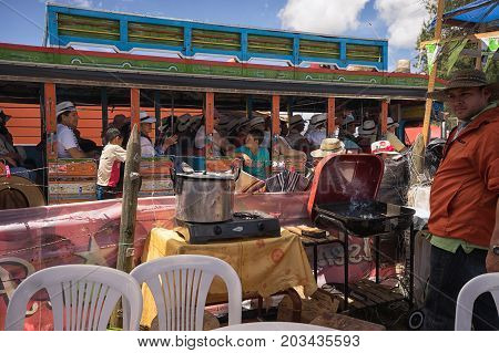 August 6 2017 Medellin Colombia: a man stands in his makeshift food stand while a bus with tourists drives by in the background