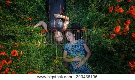 Young beautiful smiling women in ornamented ethnic sundress and silver gray tunic lay on summer blooming poppy flower field. Top view.