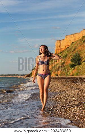 Slender Woman In Swimsuit Walks In Sea Surf