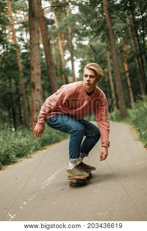 Handsome Young Man In A Pink Sweater Skates On A Skateboard. The Concept Of A Healthy Lifestyle