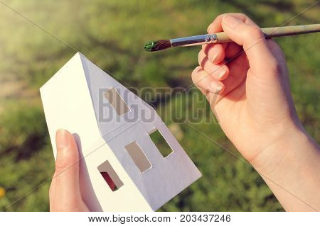 artist paints the layout of the house with a fine tassel / green color solution