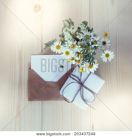 gift with a bouquet of chamomiles and an open letter for wishes on the table top view/ set for holiday