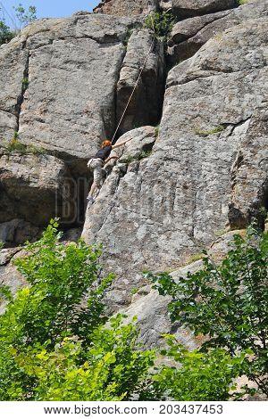 Woman Rock Climber Climbs On A Rock