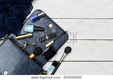 Handbag and cosmetics on a white wooden background. Mockup