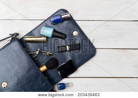 Bag of dark blue color and cosmetics on a white wooden background. View from above