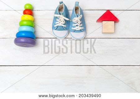 baby sneakers and wooden toys. Copy space