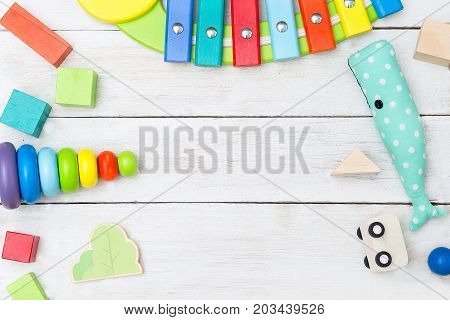 Wooden cubes and a pyramid and toy whale on a white wooden background. Copy space