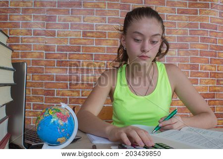 Young girl student sitting between books and calculate. Student Young Girl with bills and calculator in the room at home