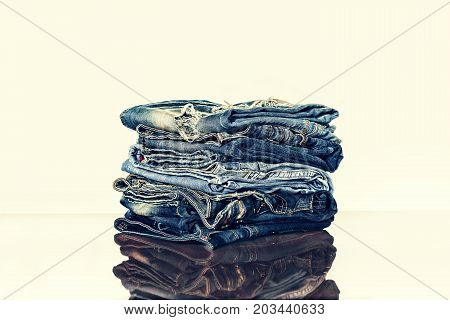 A pile of jeans on the shelf of the store or on the table. Reflection. The concept: the sale in the store clothes