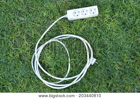 Electric Multiple Socket On A Green Grass. Green Energy Concept