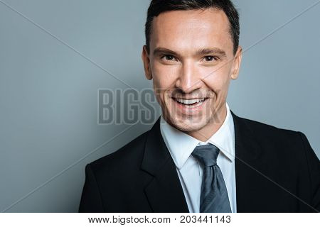 Handsome face. Happy pleasant handsome man smiling and looking at you while being in a good mood