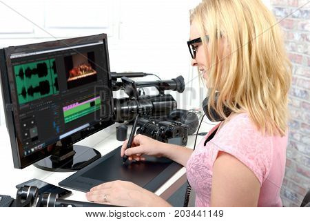 young blond woman designer using computer for the video editing