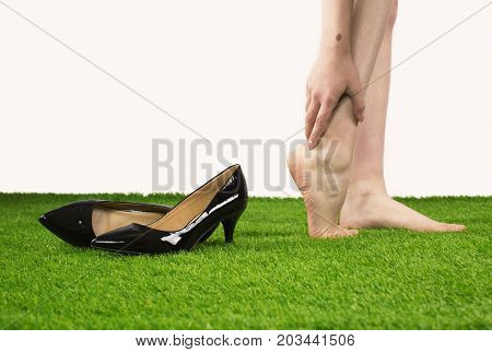 Foot Pain Woman Staying On The Grass Holding Her Feet. Health Concept.