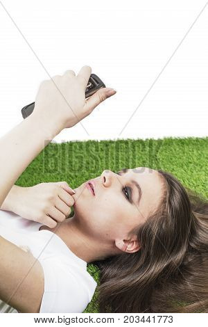 Pensive Beautiful Lady Lies On The Grass. Beautiful Young Woman With Long Hair Using And Touching Ce