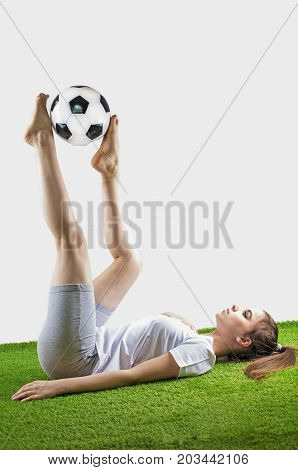 Pretty women's soccer. Young brown-haired woman in sportswear lies with a soccer ball on the grass isolated on gray background