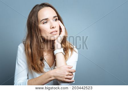 Too many thoughts. Cheerless nice thoughtful woman holding her cheek and thinking about her life while sitting against grey background