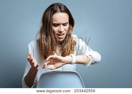 I am late. Unhappy nice positive woman looking at her watch and checking the time while being late for an appointment