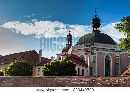 Summer sunny picture of the Church of the Assumption of the Virgin Mary and St. Charles the Great with few clouds.