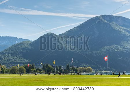Annecy France - May 25 2016: A large open space surrounds the Annecy lake where people were enjoying the spring sunshine.