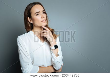 Food for thought. Attractive pleasant thoughtful woman pressing a finger to her chin and thinking while looking for a solution to the problem