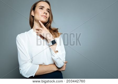 Pleasant dreams. Nice delighted dreamy woman smiling and touching her chin while dreaming about pleasant things
