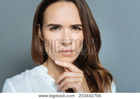 Suspicious look. Serious smart nice woman holding her chin and looking at you while feeling suspicious