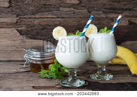 Milk banana smoothies on old wooden background