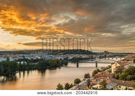 Light sunset over Vltava river with Railway bridge and Prague castle in the background. Moody sky with dramatic clouds. Summer twilight in Prague Czech Repubic
