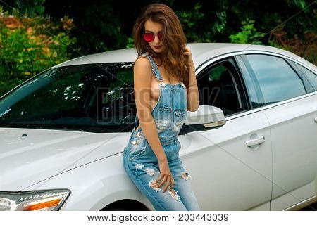 young sensual Sexy brunette stands near a car