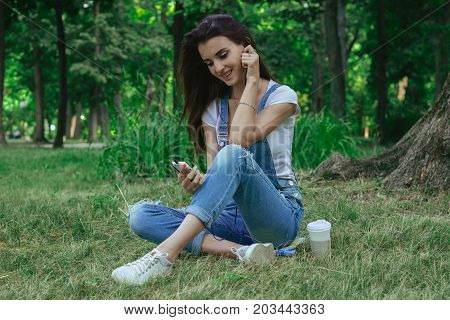 happy pretty girl sits on the grass smiles and listens to music with headphones
