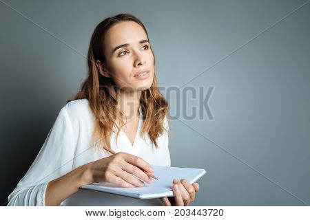 Sudden inspiration. Thoughtful beautiful nice woman holding her notebook and taking noted while being inspired