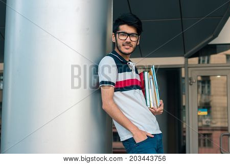 smiling nice guy stands near the columns keeps books and looking directly