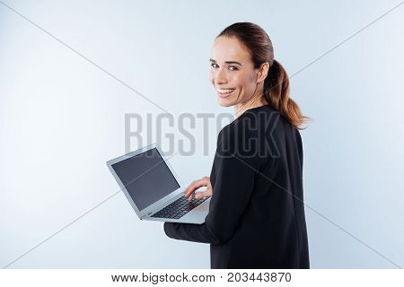 Positive mood. Cheerful pleasant young woman turning to you and smiling while holding her netbook