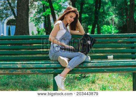 beautiful young lady in jeans dress sitting in a park and looking at laptop