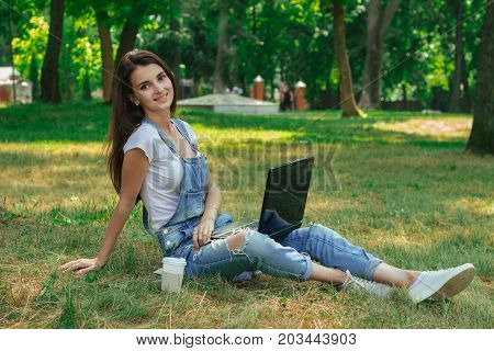 joyful pretty lady sitting on the grass in the park with a laptop looking at the camera and smiles
