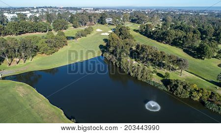 Aerial view of golf course dam with fountain surrounded by fairways, trees and bunkers