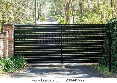 Black wrought iron security driveway gates leading to rural property