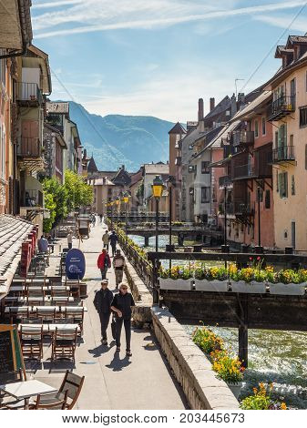 Annecy France - May 25 2016: People walking along river Thiou in city centre of Annecy capital of Haute Savoie province in France. Annecy is known to be called the French Venice.